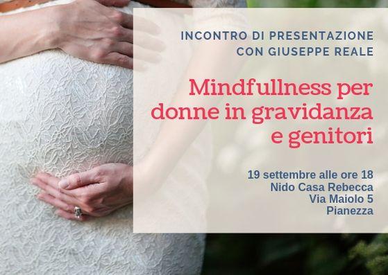 Madre accarezza pancione nel percorso mindfulness per donne in gravidanza e genitori